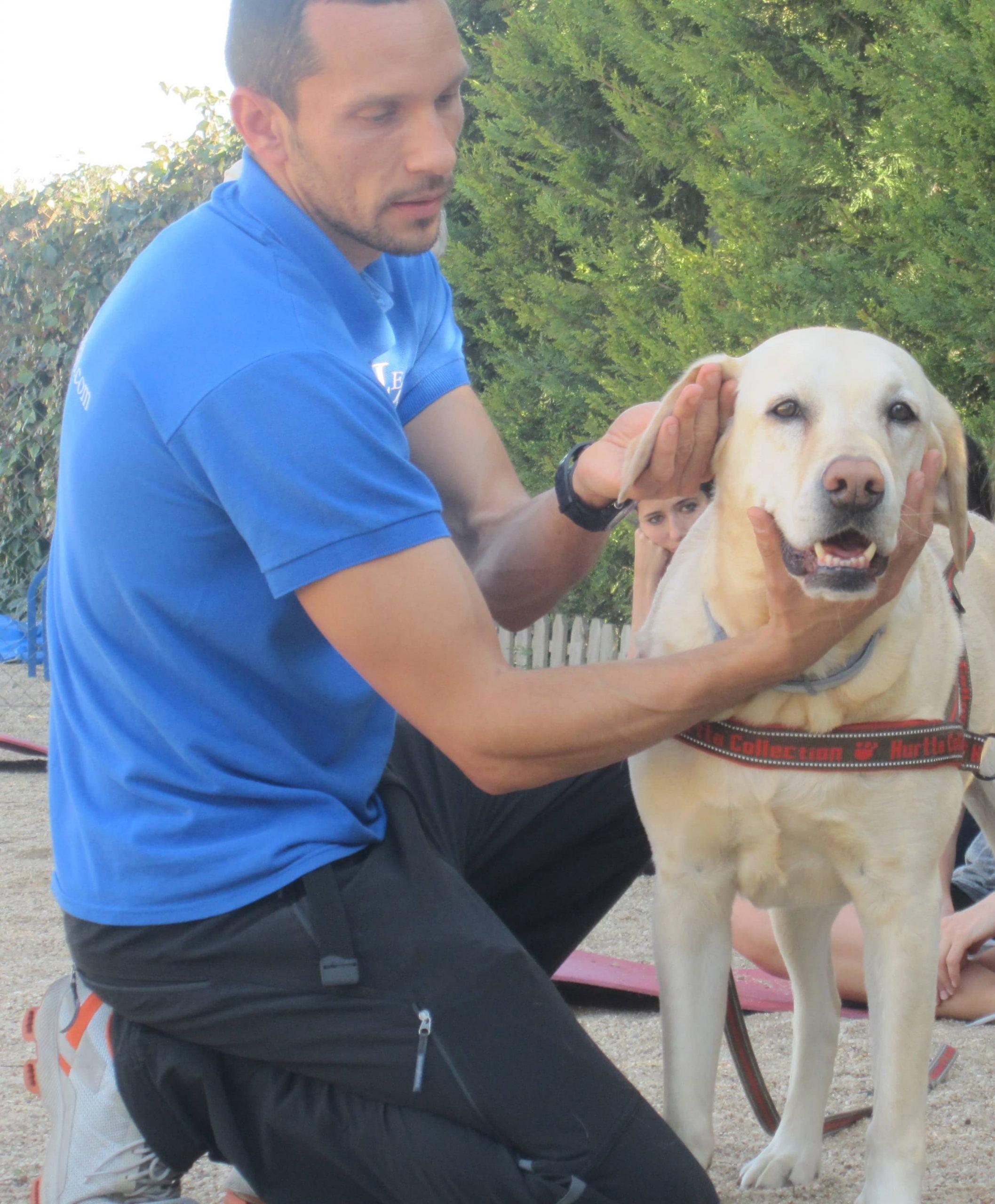 Enrique Solís apoyando la pierna derecha en el suelo, mirando y tocando con la mano derecha la barbilla y con la mano izquierda la oreja derecha de su perro Dogma que está enfrente suyo mirando a la cámara